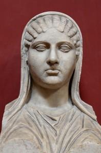 Statue représentant Aspasie vêtue d'une tunique et portant un voile sur ses cheveux.