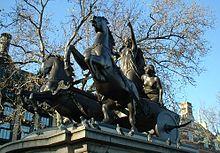 Photographie d'une statue représentant Boadicée ou Boudicca sur un char tiré par deux chevaux les pattes en l'air. Elle est accompagnée de ses deux filles.