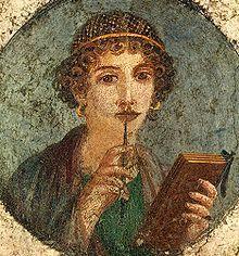 Cette image représente une femme qui pourrait être Sapphô. Elle porte ses cheveux bouclés sous une coiffe, une tunique verte et brune et des boucles d'oreille dorées. Elle tient un livre et un pinceau.