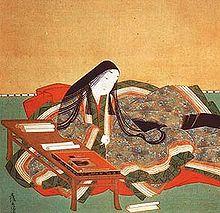 Représentation de Murasaki Shikibu assise devant une table de travail sur laquelle sont étalés des rouleaux