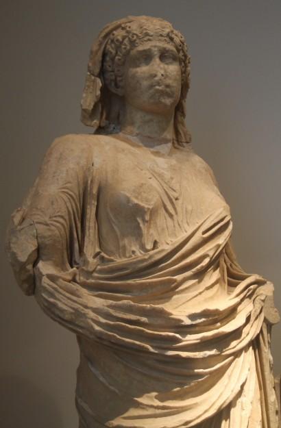 Statue d'Agrippine la jeune portant une tunique et une coiffe sur ses cheveux bouclés