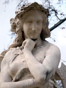 Photographie d'une statue représentant la prophétesse Velléda. Elle porte une sorte de tunique dévoilant sa poitrine et semble pensive, une main sous le menton