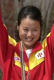 Photographie de Zhang Shan en tenue sportive rouge et jaune, souriante, les bras levés. On voit les cordons de sa médaille d'or autour de son cou.