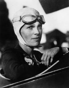 Photographie en noir et blanc d'Amelia Earhart aux commandes d'un avion. Elle porte un bonnet d'aviatrice et des lunettes d'aviatrice remontées sur le front.
