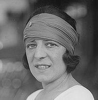 Photographie en noir et blanc de Suzanne Lenglen. Elle porte un large bandeau de tissu autour de sa tête et de ses cheveux sombres et courts, et sourit à moitié.