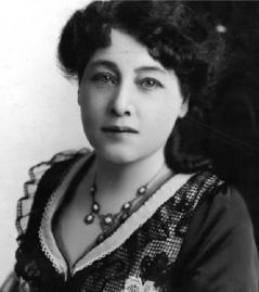 Photographie en noir et blanc d'Alice Guy portant une robe à dentelle et un collier