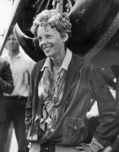 Photographie en noir et blanc d'Amelia Earhart, qui se tient debout, les mains sur les hanches, devant le réacteur d'un avion. Elle sourit.