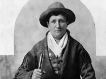 Photographie en noir et blanc de Calamity Jane en veste à franges et portant un chapeau. Dans sa main droite, on voit le bout de sa carabine