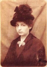 Phoptographie de Camille Claudel portant une veste sombre et un chapeau noir à plumes. Elle a une expression grave et sérieuse