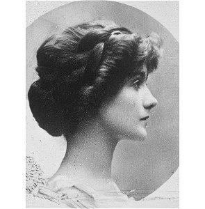 Portrait de Coco Chanel dans sa jeunesse. De profil, elle regarde vers la droite et ses cheveux bruns sont retenus dans un chignon élaboré.