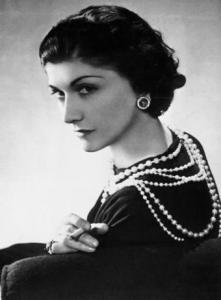 Photographie en noir et blanc de Coco Chanel. Vêtue d'une robe noire, elle porte un collier de perles multirangs, des boucles d'oreille, et fume une cigarette