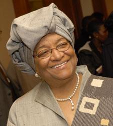 Photographie d'Ellen Johnson Sirleaf. Elle porte un collier de perles et un foulard autour de la tête. Elle sourit.