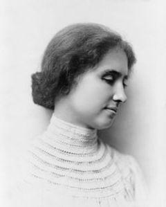 Photographie en noir et blanc d'Helen Keller de profil. Ses cheveux sont noués en chignon et elle porte un vêtement blanc à col montant