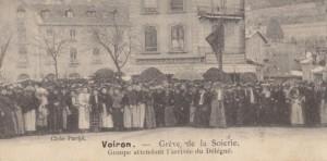 """Photographie de la grève de Voiron montrant la foule des grévistes en train d'attendre sur une place, devant des bâtiments. La légende dit : """"Voirin - grève de la scierie. Groupe attendant l'arrivée des délégués""""."""