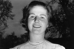 Photographie en noir et blanc de Margaret Thatcher dans sa jeunesse. Elle est en extérieur, devant des arbres, et sourit.