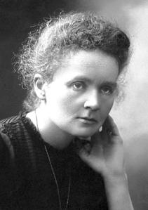 Photographie en noir et blanc de Marie Curie portant un vêtement sombre. La main gauche portée à son visage, elle semble pensive