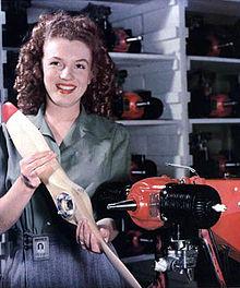 Photographie de Marilyn Monroe en 1945, alors qu'elle travaille dans une usine de drones. Souriante, elle porte une salopette bleue et une chemise verte et tient des pièces techniques à la main.