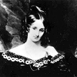 Portrait de Mary Shelley portant une robe noire au décoleté décoré de fleurs claires. Elle penche légèrement la tête et porte ses cheveux sombres en boucles anglaises