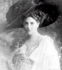Photographie en noir et blanc de Mata Hari. Elle porte une robe blanche et un chapeau noir aux bords très larges