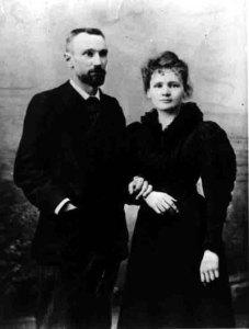 Photographie en noir et blanc de Marie et Pierre Curie, tous deux vêtus de noir et se tenant par le bras