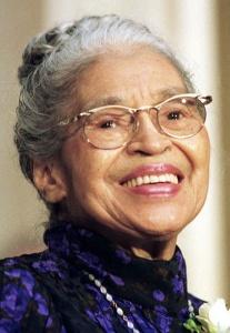 Photographie de Rosa Parks âgée, ses cheveux grisonnants retenus en chignon. Elle porte des lunettes et a un large sourire.