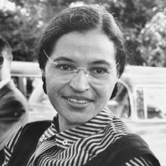 Photographie en noir et blanc de Rosa Parks portant une chemise rayée. Elle sourit.