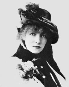 Portrait de Sarah Bernhardt portant des fleurs sur la poitrine et un chapeau sombre décoré de plumes