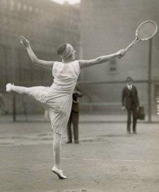 Photographie de Suzanne Lenglen jouant au tennis. Elle tient une raquette au bout de son bras droit tendu et sa jambe gauche est levée toute droite, parallèle au sol