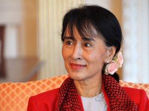 Photographie d'Aung San Suu Kyi assise sur un canapé. Elle porte une veste et un foulard rouges et des fleurs dans ses longs cheveux noirs.