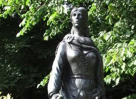 Photographie d'une statue représentant Grace O'Malley. Elle est représentée portant une cape et une robe lacée sur la poitrine.