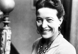 Photographie en noir et blanc de Simone de Beauvoir. Elle porte un collier et de larges boucles d'oreille, et ses cheveux sont retenus en chignon. Elle a un large sourire.