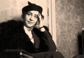Photographie en noir et blanc d'Hannah Arendt jeune. Assise, elle a la main gauche appuyée contre son visage et porte un béret.