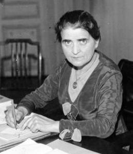 Photographie en noir et blanc de Suzanne Lacore. Assise à son bureau, elle tient un stylo à la main et regarde la caméra.