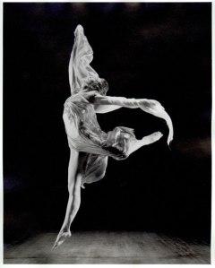 Photographie en noir et blanc d'Isadora Duncan en plein mouvement de danse. Elle saute, une jambe droite et l'autre levée vers l'arrière, les deux bras écartés.