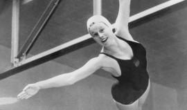 Photographie en noir et blanc de Marjorie Gestring en tenue de bain, maillot de bain et bonnet de bain. La photo est prise en pleine plongeon et Marjorie Gestring, les bras écartés et les jambes jointes, flotte dans l'air.