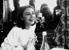 Photographie en noir et blanc d'Audrey Hepburn en train de rire. Derrière elle, on voit cinq garçons derrière une fenêtre.