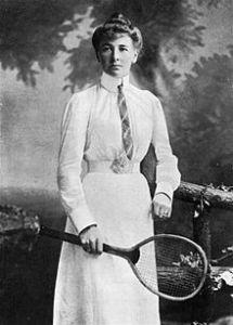 Photographie en noir et blanc de Charlotte Cooper portant une jupe et une chemise blanches, avec une raquette de tennis à la main