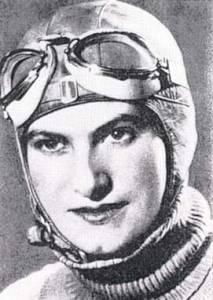 Photographie en noir et blanc d'Hélène Boucher montrant son visage. Elle porte une cagoule et des lunettes d'aviatrice sur le front.
