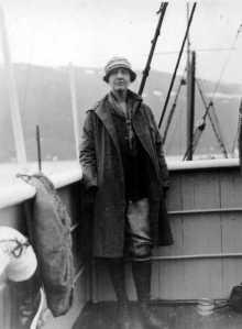 Photographie en noir et blanc de Louise Boyd debout sur son bateau, appuyée contre la balustrade