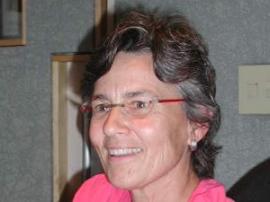 Photographie d'Ann Bancroft souriante. Elle a les cheveux sombres courts et porte des lunettes.
