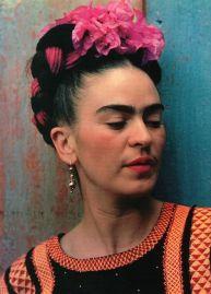 Photographie de Frida Kahlo. Ses cheveux noirs sont retenus dans une coiffure élaborée avec une couronne de fleurs roses.