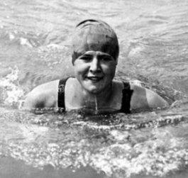 Photographie en noir et blanc de Gertrude Ederle dans l'eau. Sa tête et ses épaules émergent, et elle porte un bonnet de bain.