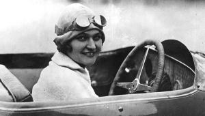 Photographie en noir et blanc d'Eliška Junková au volant de son automobile