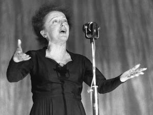 Photographie en noir et blanc d'Edith Piaf en train de chanter, debout devant son micro, les bras écartés devant elle