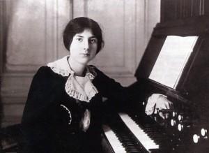 Photographie et noir et blanc de Lili Boulanger vêtue d'une robe noire et assise devant son piano, un bras posé sur les touches.