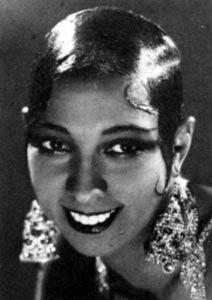Photographie en noir et blanc de Josephine Baker souriante en tenue de scène