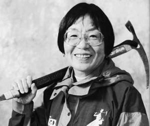 Photographie en noir et blanc de Junko Tabei souriante et portant un piolet sur l'épaule
