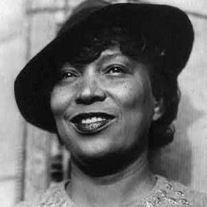 Photographie en noir et blanc de Zora Neale Hurston souriante et portant un chapeau