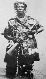 Photographie en noir et blanc de Yaa Asantewaa portant une arme