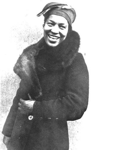 Photographie en noir et blanc de Zora Neale Hurston souriante en manteau d'hiver